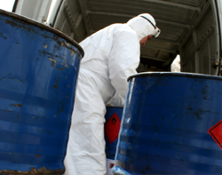 workers in ppe hazardous waste drums