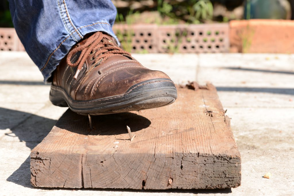Here is a picture of a construction worker stepping on an exposed nail, a common workplace hazard.